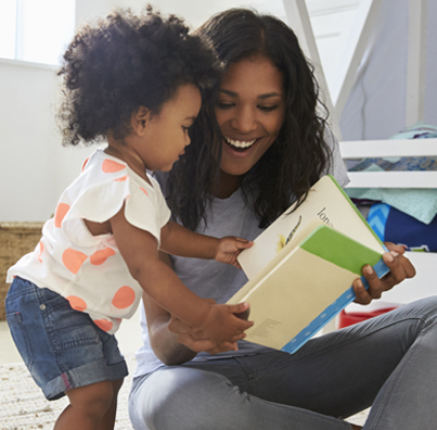 A smiling mother sits and reads a children's book with her daughter