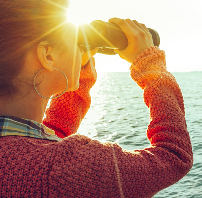 woman looking through binoculars at body of water