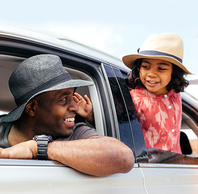 Man and young daughter wearing hats and smiling to each other while sitting in a car