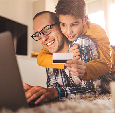 Father on computer with son hugging and holding credit card