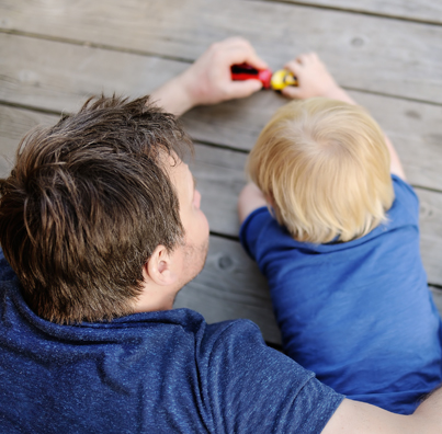 Father and young child play with toy cars
