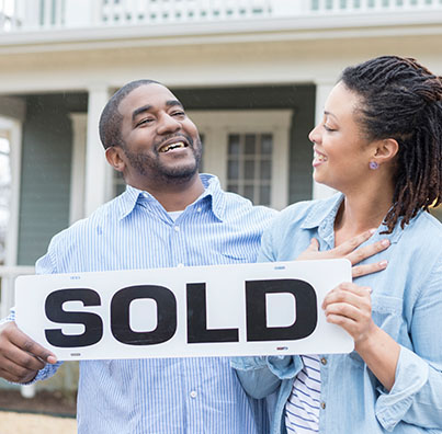 man and woman smiling holding a SOLD sign for house