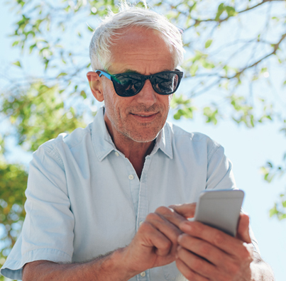 Smiling man with sunglasses using smartphone