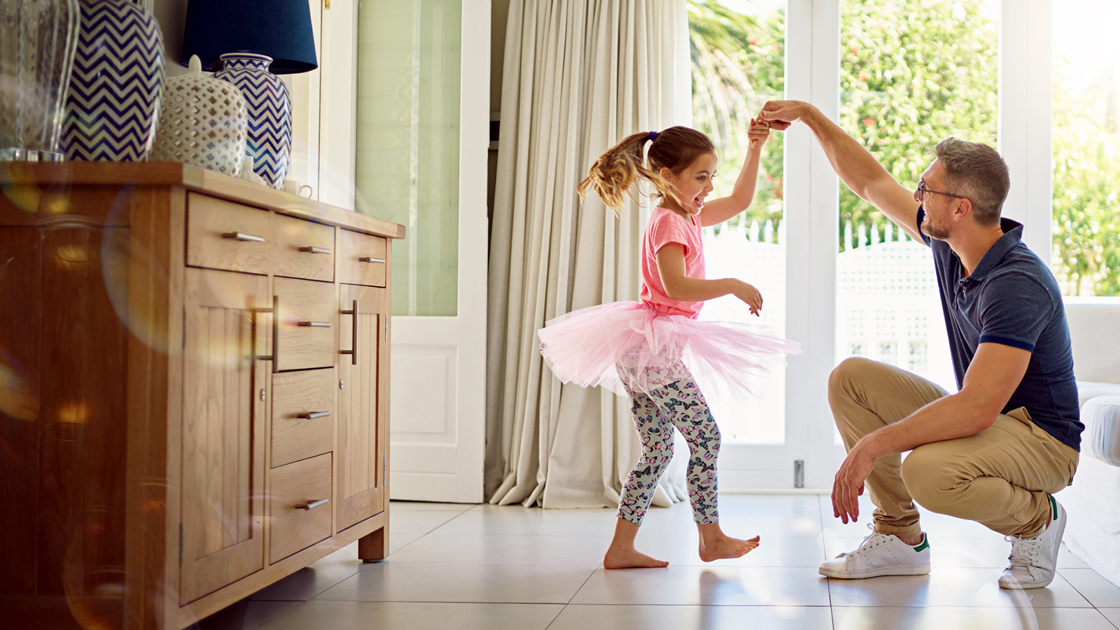 Father spinning daughter dressed in a tutu