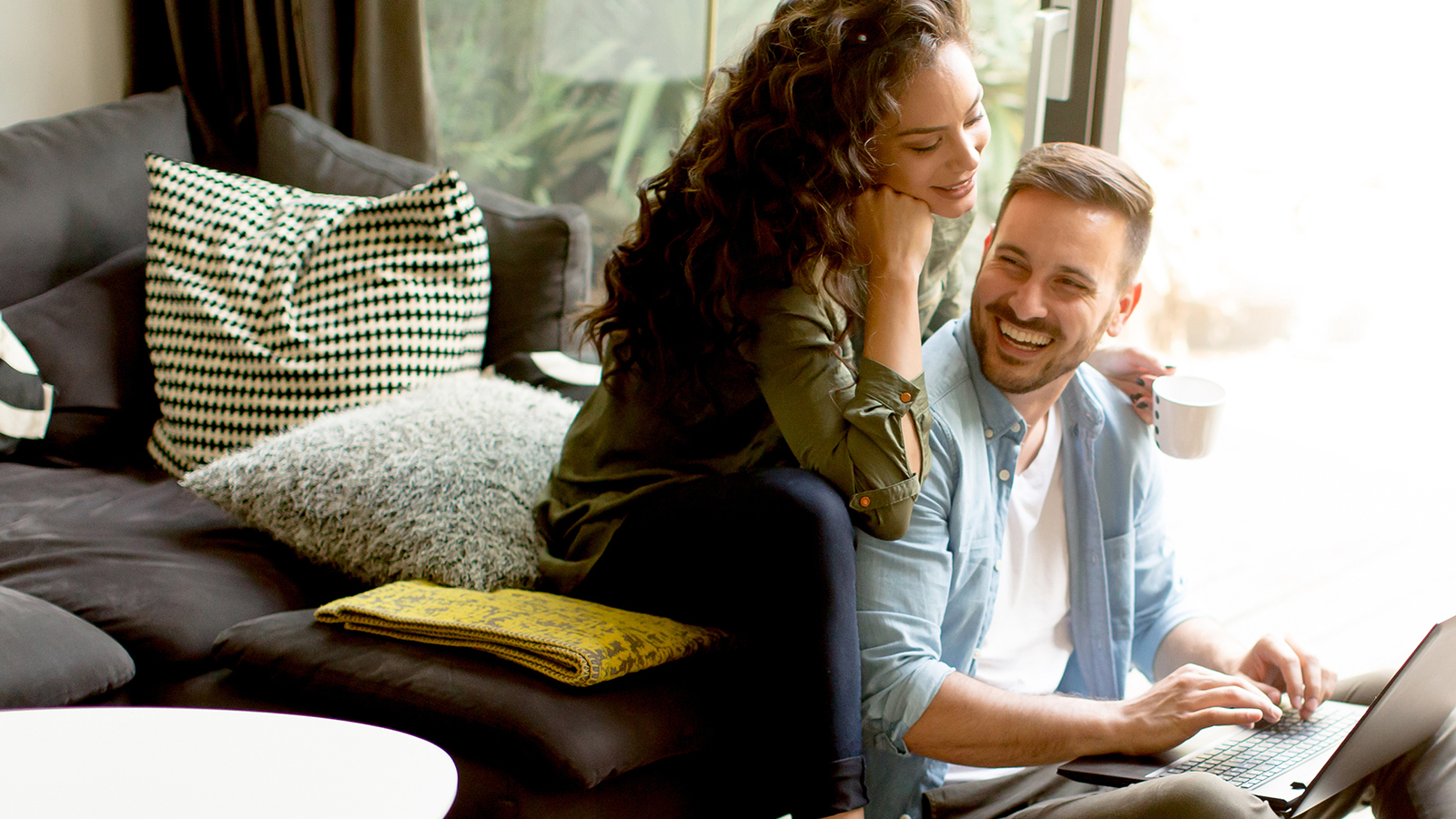 A laughing man on a computer with a woman leaning on his shoulders