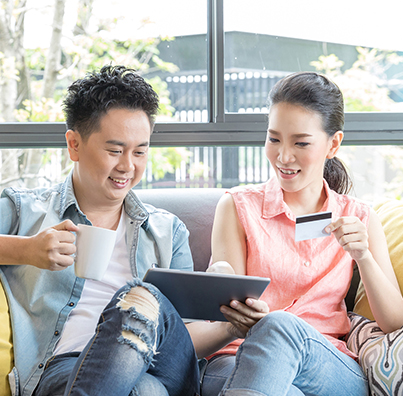 Sitting man with mug and woman with credit card use tablet